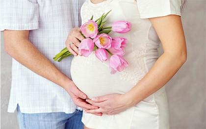 беременная с цветами и мужчиной