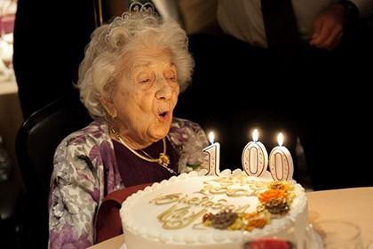бабушка задувает свечи на торте