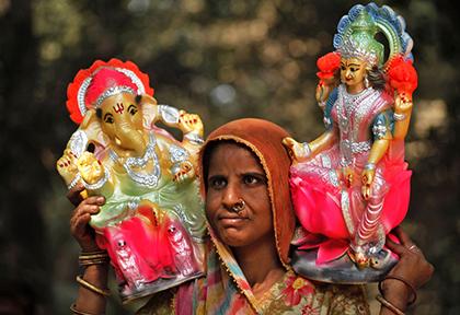 женщина несет статуэтки Лакшми и Ганеша